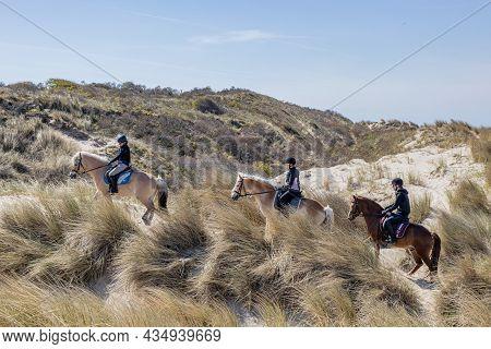 Renesse, Schouwen-duiveland, Zeeland Province, Netherlands. April 26, 2021. Three Young Helmeted Rid