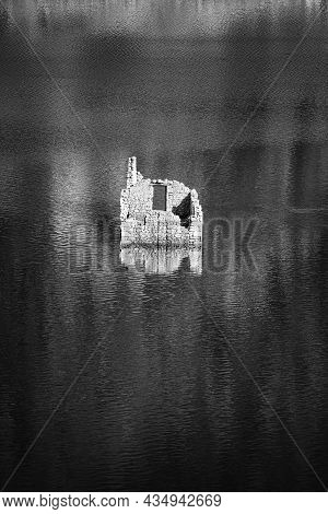 Black And White View Of An Ancient House Remains Emerged From A Lake