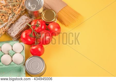 Food Donations On Yellow Background With Copy Space - Pasta, Vegatables, Canned Food, Cooking Oil. F