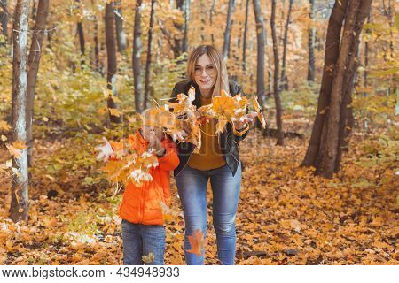Single Parent Family Playing With Autumn Leaves In Park. Happy Mom And Son Throw Autumn Leaves Up In