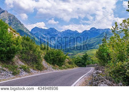 Summer Landscape - Valley And Road In Albanian Mountains, Green Trees And Gray Clouds On The Sky