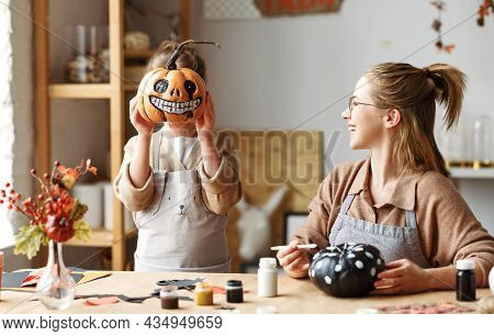 Little Girl Holding Spooky Halloween Pumpkin In Front Of Face While Preparing For Halloween With Mom