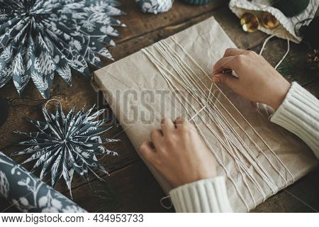Wrapping Christmas Gift. Hands Wrapping Stylish Simple Xmas Gift In Craft Paper With String On Rusti