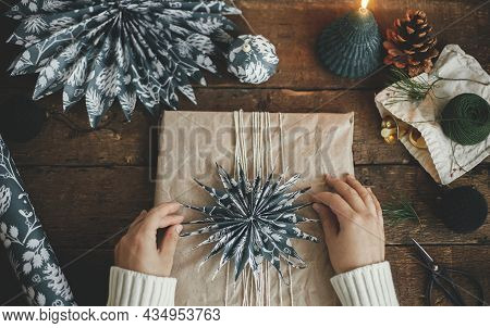 Christmas Gift Rustic Flat Lay. Hands Decorating Stylish Xmas Gift In Craft Paper With Blue Paper St