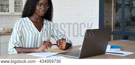 Young Intelligent African Black Businesswoman Student In Glasses Sitting At Desk Watching Online Lea