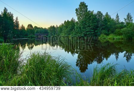 July Evening On The Bank Of A Quiet River Leisurely Fishing Blurred Reflection Of The Forest.
