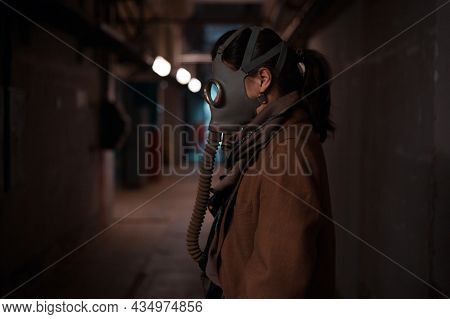 A Post-apocalyptic Concept. A Woman In A Gas Mask Escapes From Chemical Contamination Or A Biologica