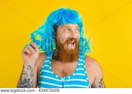Amazed Man With Life Buoy, Swimsuit And Blue Wig Acts Like A Amazed Woman