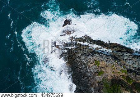 Aerial View Top Down Seashore Big Wave Crashing On Rock Cliff Beautiful Dark Sea Surface In Sunny Da