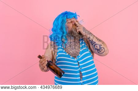 Fat Man With Beard And Wig Smokes Cigarettes And Drinks Beer