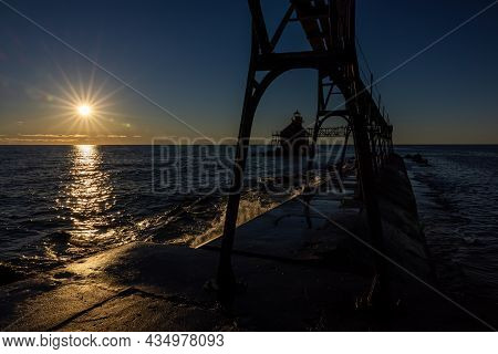 A Silhouetted Breakwater Lighthouse On Lake Michigan At Sunrise.