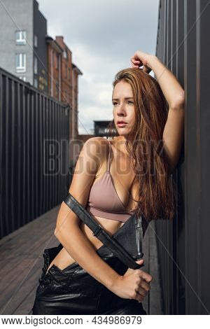 Creative Portrait Of A Red-haired Woman In  Leather Overalls And Top . Design Concept. Romantic Port