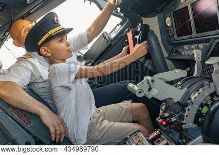 Little Boy In A Pilot Cap In The Cockpit