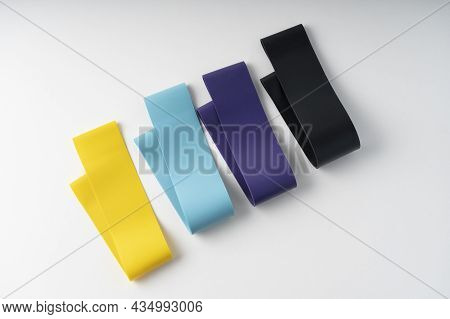 A Set Of Colorful Elastic Fitness Band. Expanders For Women And Weight Loss On White Background Flat