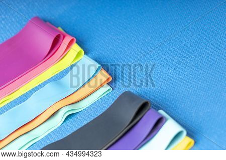 A Set Of Colorful Elastic Fitness Band. Expanders For Women And Weight Loss On A Blue Background Fla