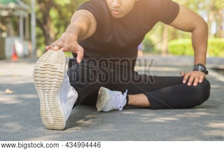 Young Fitness Man Runner Stretching Before Run. Healthy Fitness, Workout, Sport, Lifestyle And Sport