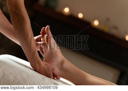 Masseur Doing A Foot Massage With Candles On Background