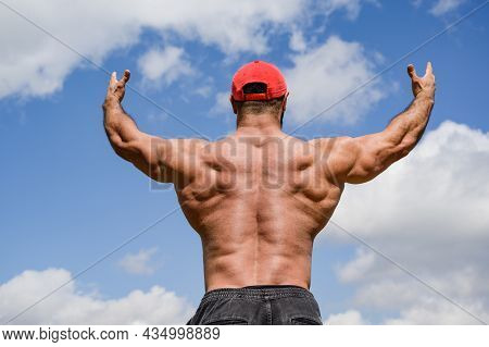 Strong Young Sport Male In Red Cap Rising Hands To Blue Skies Showing Strong And Powerful Back Muscl