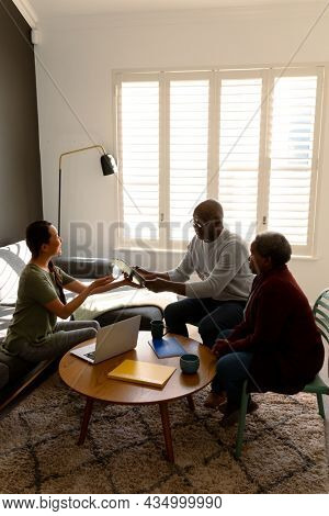 African american senior couple having meeting with asian female counselor at home. retirement lifestyle, elderly support and spending time at home.