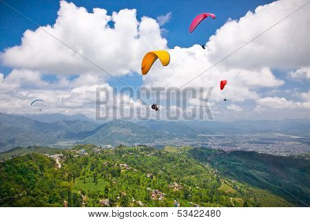 Paraglider flying against the Himalayas , Pokhara , Nepal.