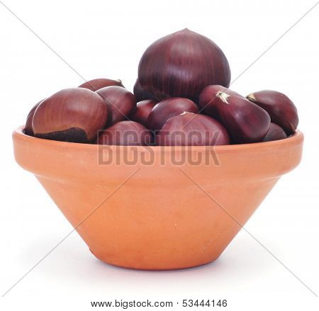 an earthenware bowl with chestnuts on a white background