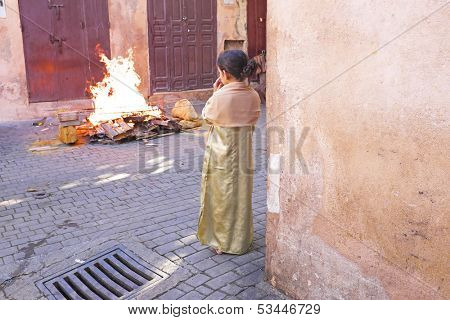 FES, MAROCCO - October 15 2013 : Girl watching the fire on Eid al-Adha. The festival is celebrated by sacrificing a lamb or other animal and distributing the meat to relatives, friends, and the poor.