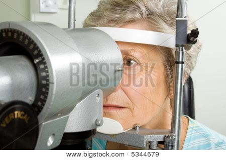 An older lady taking an eyesight test examination at an optician clinic poster