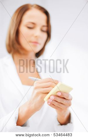 business, office, school and education concept - businesswoman writing on sticky note