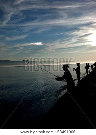 Silhouettes Fishing On The Shore
