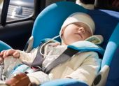 Toddler sleeping in a blue car seat poster