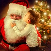 Santa Claus and Little Boy. Christmas Scene. Boy Telling Wish in Santa Claus's Ear in front of Christmas Tree  poster