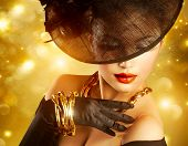 Glamour Woman Portrait over Holiday Gold Background.Luxury Golden Jewelry. Gorgeous Vogue Style Lady wearing Hat and Gloves. Jewellery. Vintage Styled Retro Girl  poster