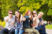 summer holidays, education, campus and teenage concept - group of students or teenagers showing thumbs up poster