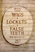 """Old fashioned sign inviting you to """"hock"""" your wigs, lockets and false teeth. poster"""