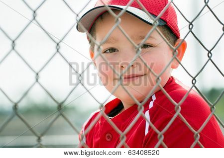 Young baseball player in uniform sitting in dugout