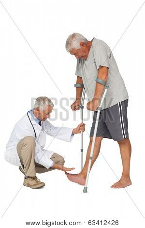 Side view of a doctor with senior man using walker over white background