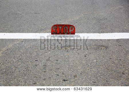 Old road stop sign mounted on asphalt