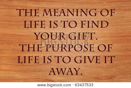 The meaning of life is to find your gift. The purpose of life is to give it away - quote by unknown author on wooden red oak background poster