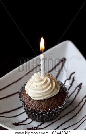 Chocolate Cupcake With A Burning Birthday Candle