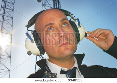 Model Looking Up With Headphones And Towers
