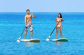 Stand up paddleboarding beach people on stand up paddle board, SUP surfboard surfing in ocean sea on Big Island, Hawaii Beautiful young mixed race Asian woman and Caucasian man doing water sport. poster