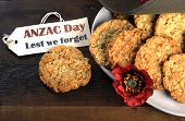 Australian army slouch hat and traditional Anzac biscuits on dark recycled wood with remembrance red poppy with Anzac Day Lest We Forget tag. poster