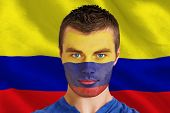 Composite image of serious young colombia fan with facepaint against digitally generated colombia national flag poster