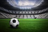 Black and white leather football in a vast football stadium with fans in white poster