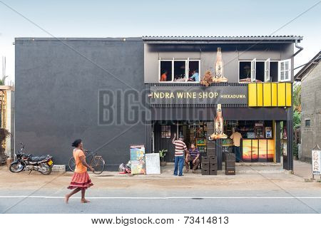 HIKKADUWA, SRI LANKA - FEBRUARY 24, 2014: Local people in front of the Indra Wine Shop. There is no wine production in Sri Lanka, mostly are available Indian, Australian and South African brands.