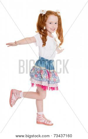 Playful little girl with hands raised simulates flight. Girl is six years old.
