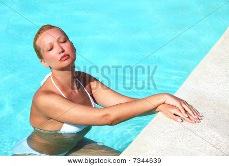 Young Female Enjoying Sun In Swimming Pool