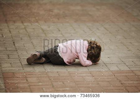 crying girl lying on asphalt