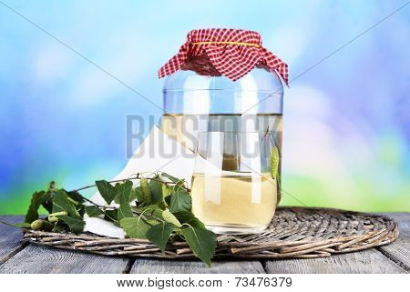 Flagon of birch juice on wicker round mat on wooden table on nature background