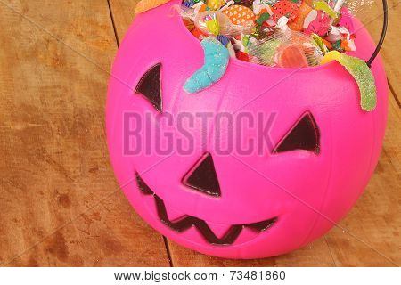 Pink plastic pumpkin filled with candy wooden table
